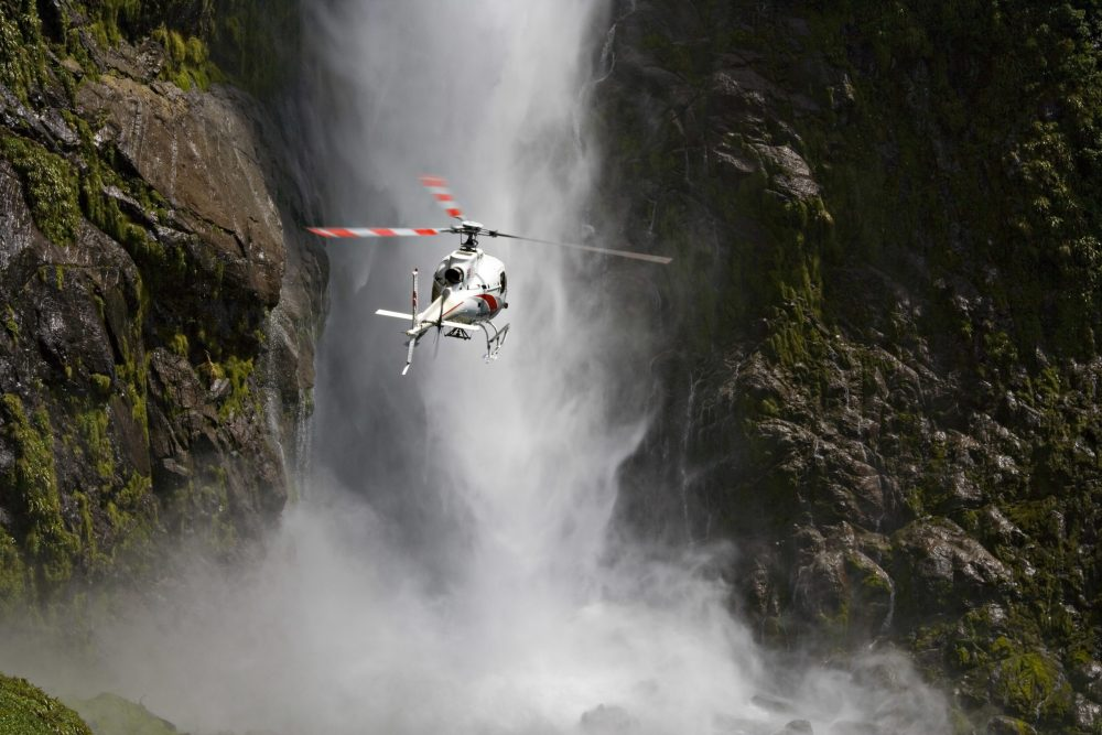 a helicopter by a dramatic waterfall
