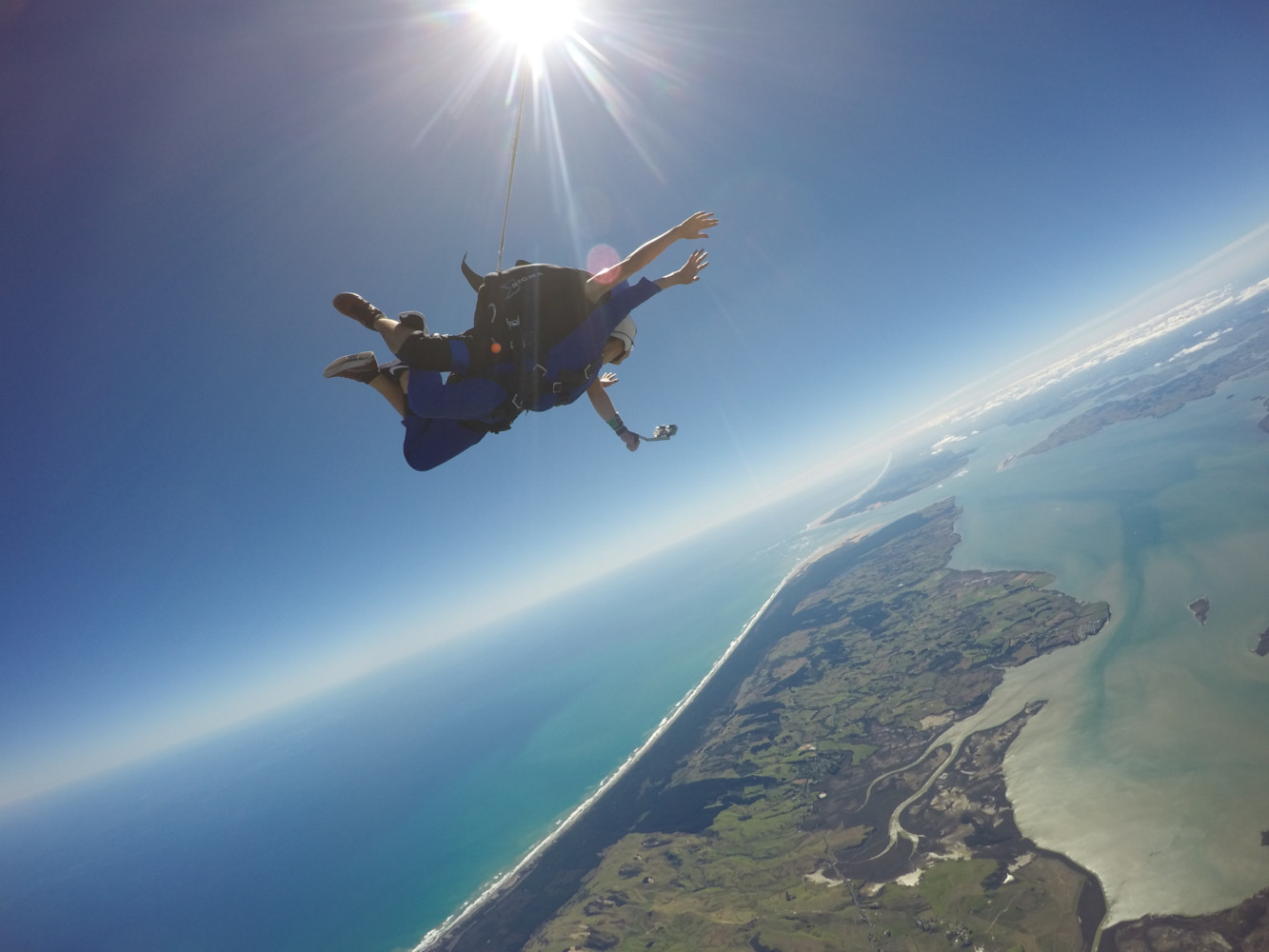 Tandem skydivers high above Kaipara Harbour and South Head