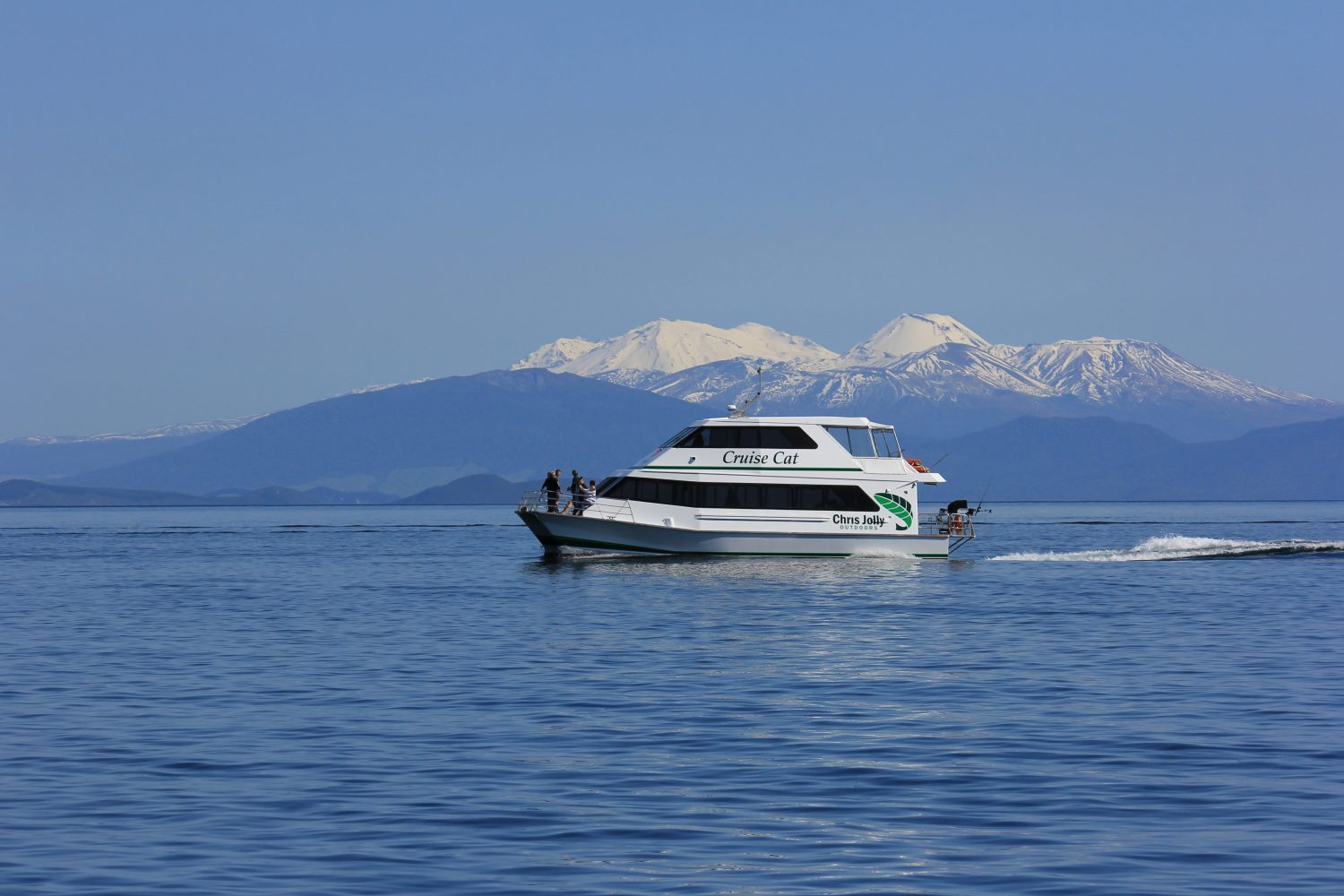 Boat on a lake with snow capped mountains behind