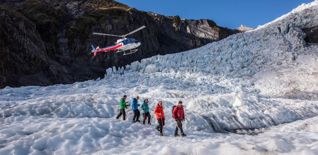 people walking on snow with a helicopter overhead