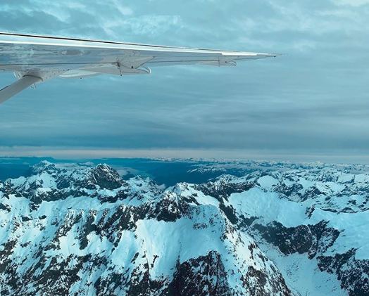 from flight view of wing over snow covered mountains