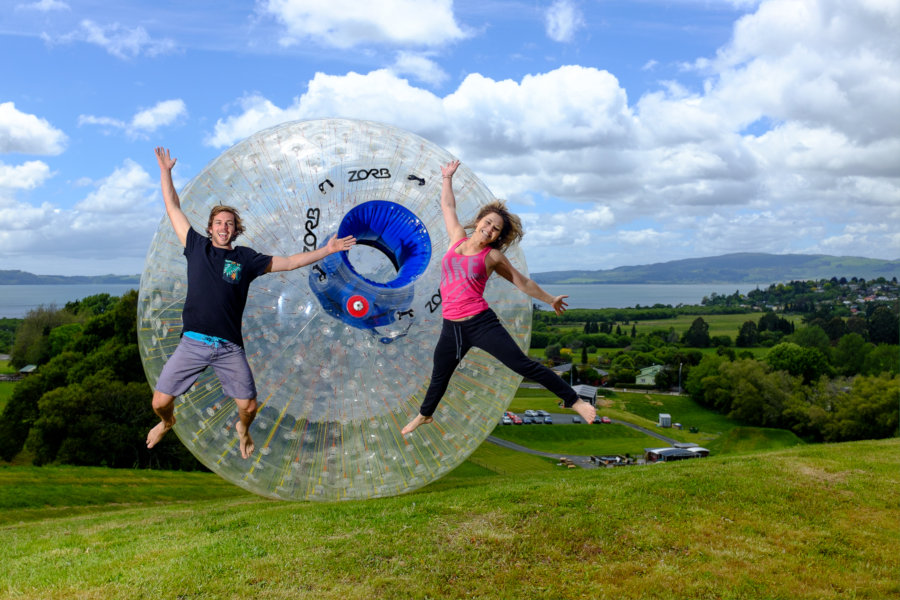 two people leaping excitedly in front of a ZORB on a hill with the lake behind