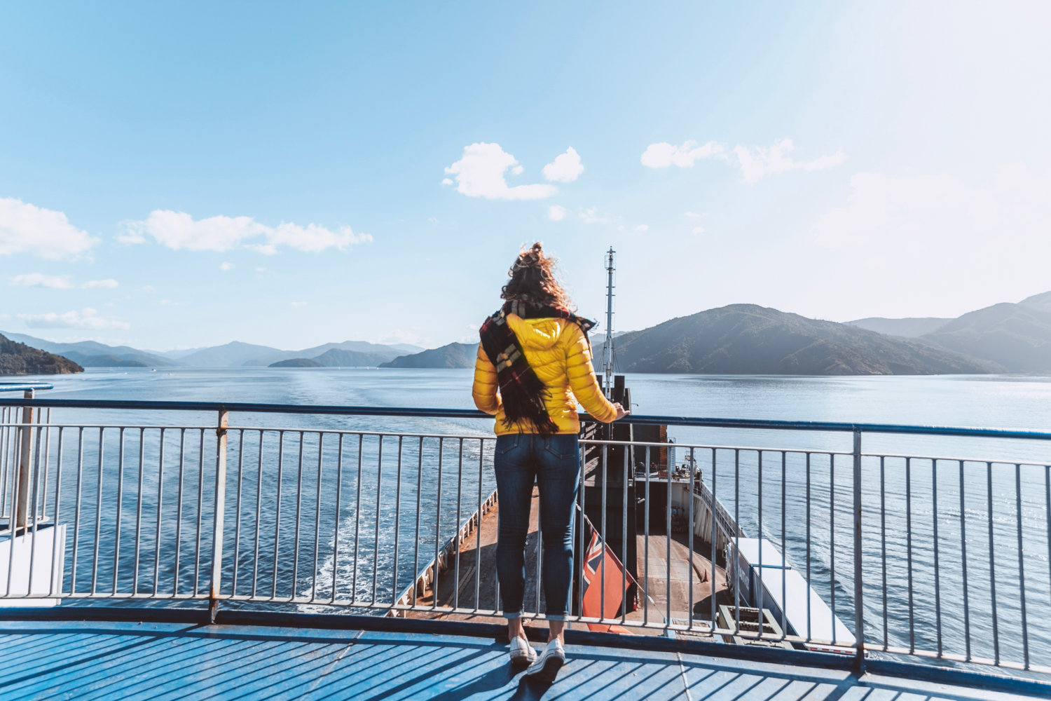 A person looking out at the Marlborough Sounds from the ferry viewing deck