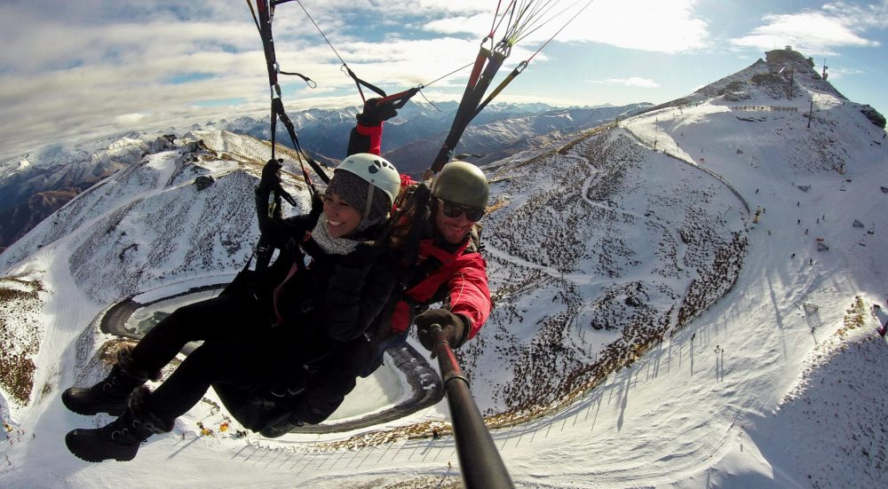 two people hanggliding against a snowy mountain and ski field backdrop