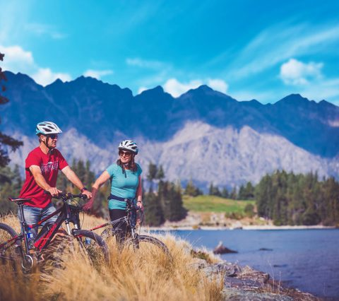 Two people with bikes by lakeshore with mountains in background