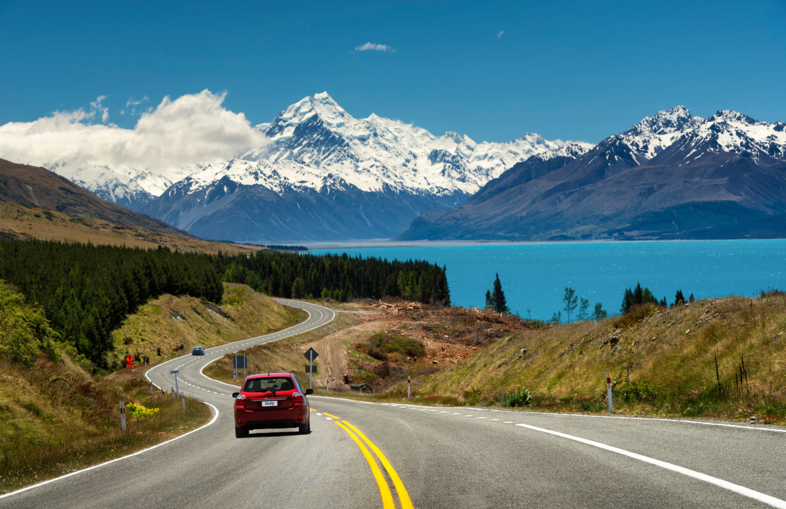 Red car on the road to Lake Pukaki and Aoraki / Mount Cook