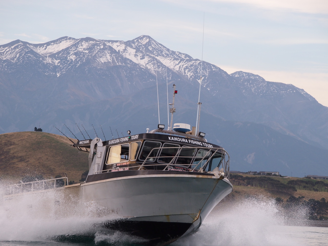 The Kaikoura Fishing Tours boat with Southern Alps in background