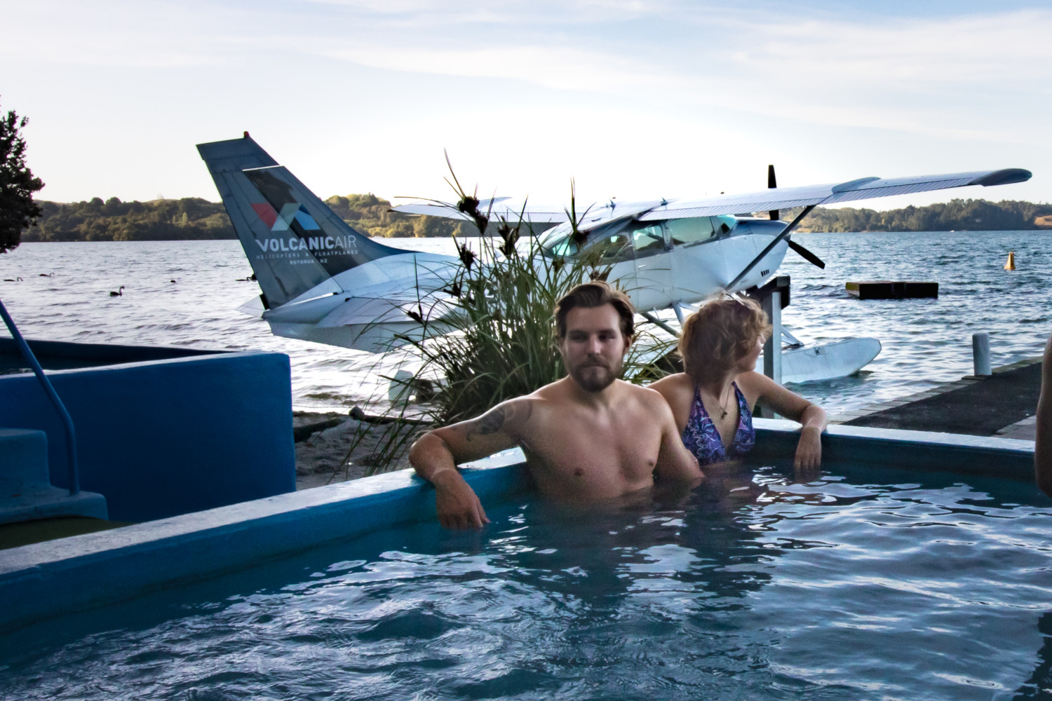 Two people in thermal pool with floatplane on lake in background