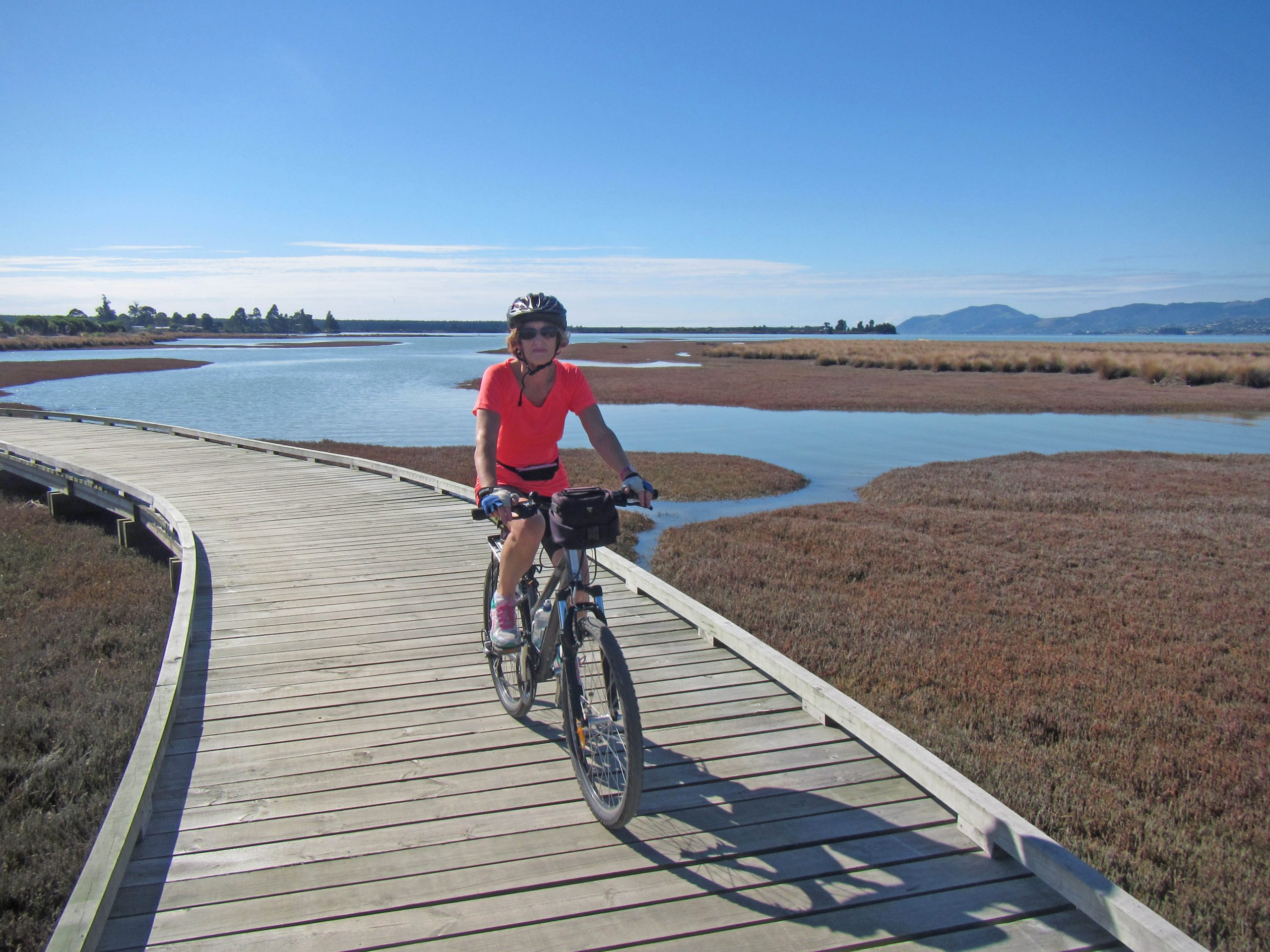 Cyclist on wooden pathway by Waimea Estuary