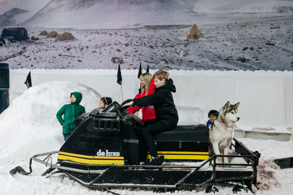Children with snowmobile and dog in snow room