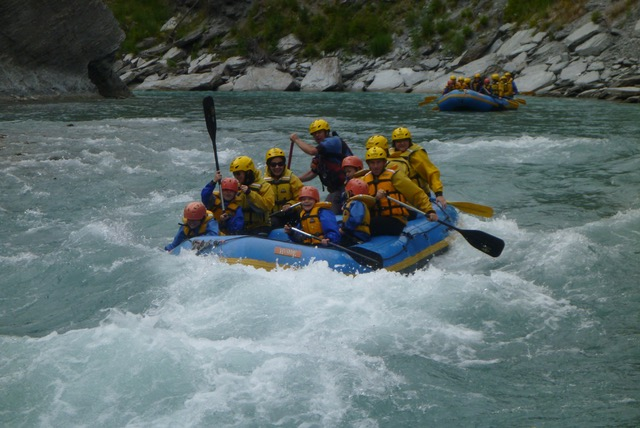 A raft full of people paddling in white water