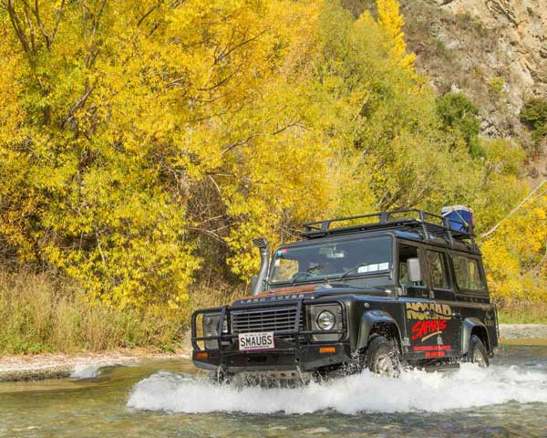 Four wheel drive vehicle driving through water in front of yellow vegetation