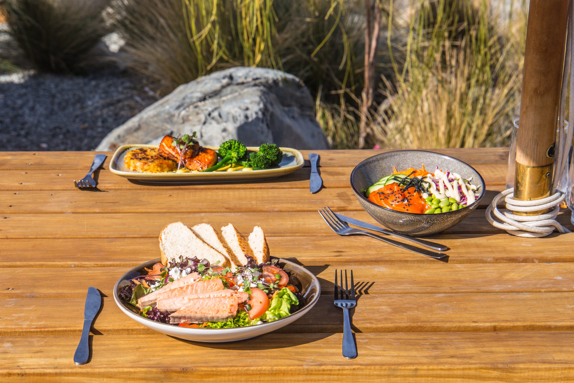 plates of fresh food on a wooden cafe table