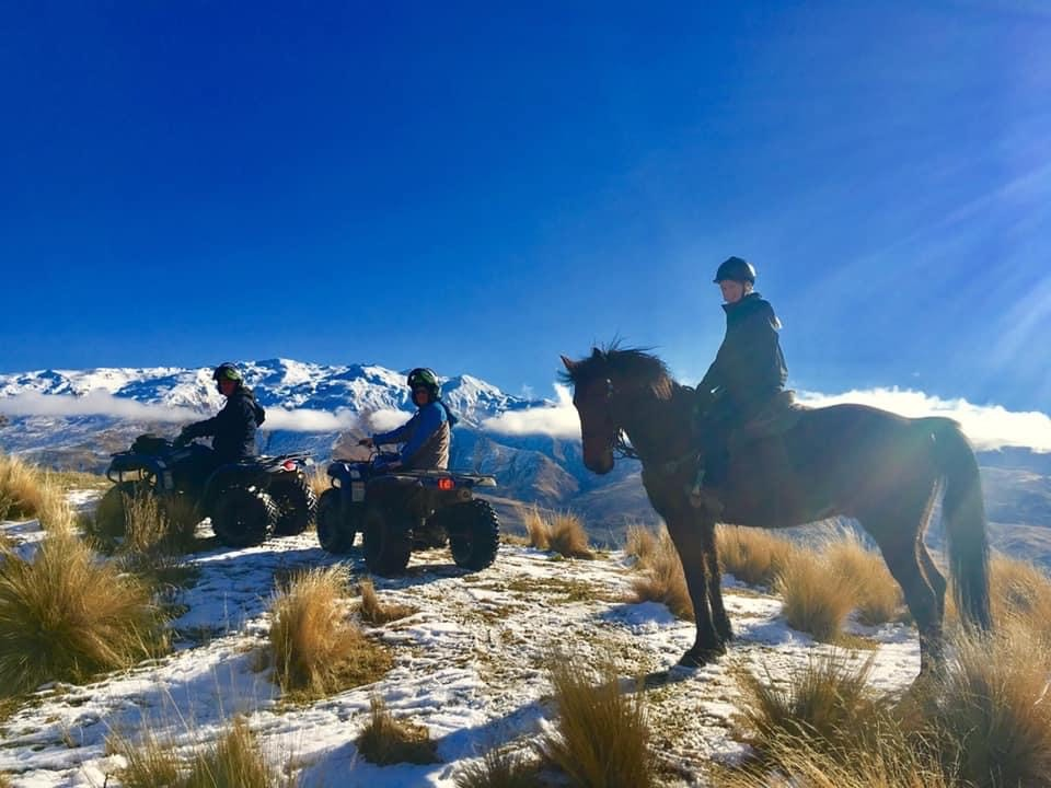 Person on horse and two people on quad bikes on a high plateu with mountains and deep blue sky in background