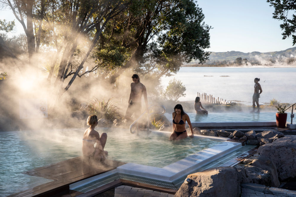 People in mineral pools with view over lake and sun illuminating steam