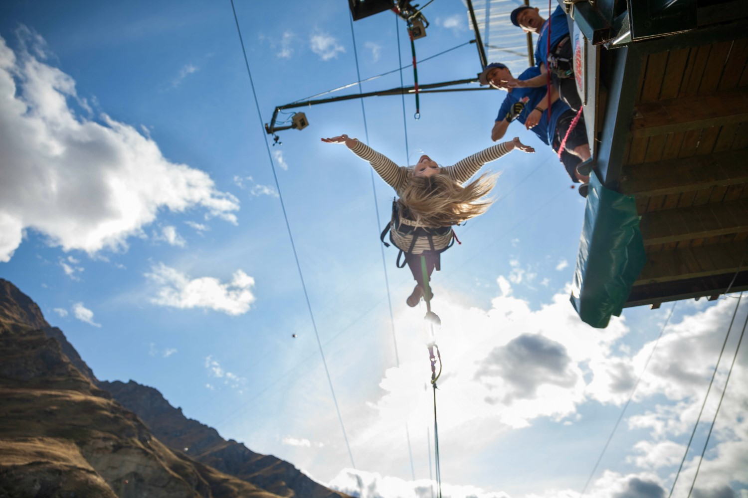 person with long blonde hair on a canyon swing