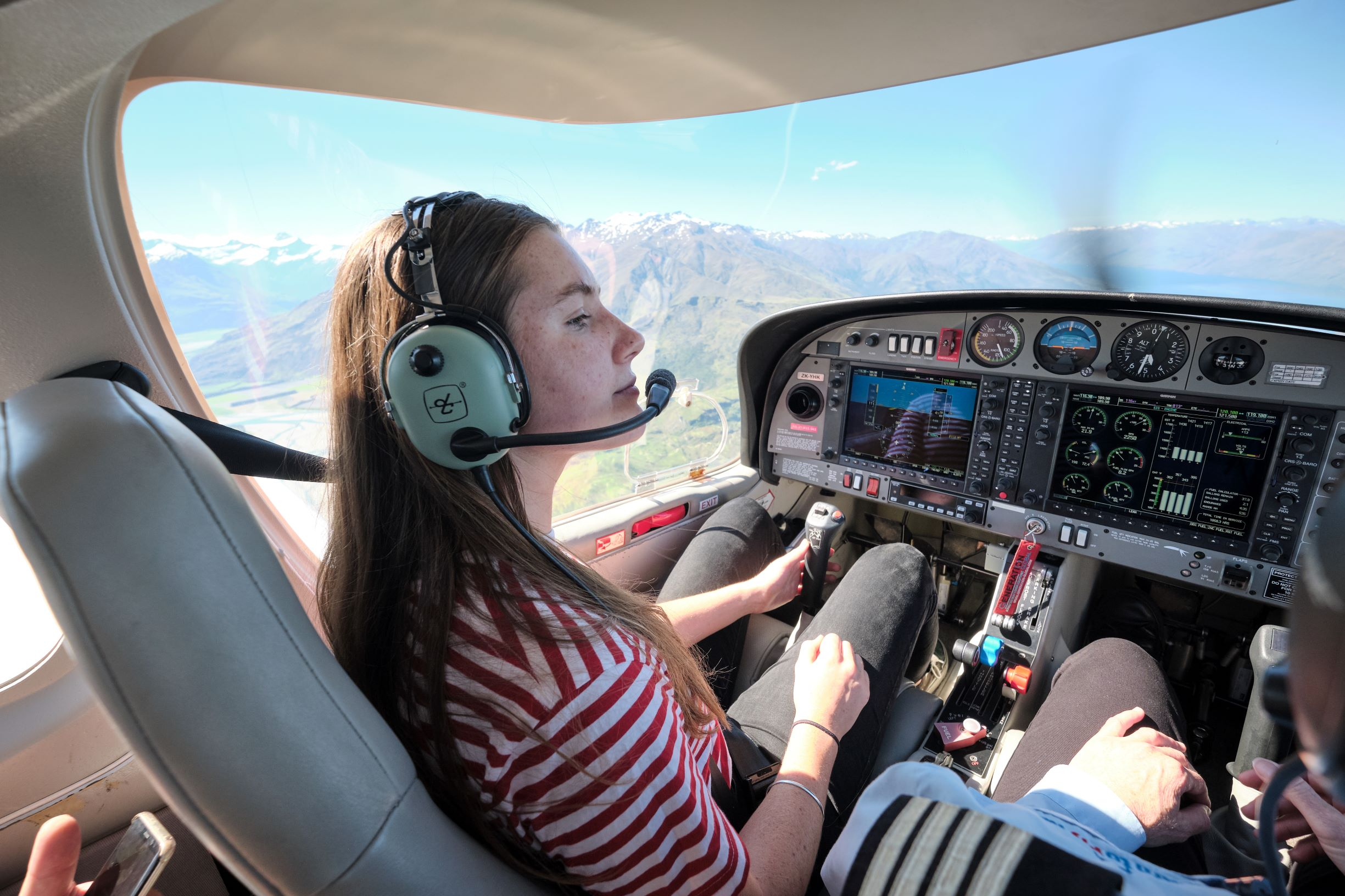 person in a cockpit with mountains in the background