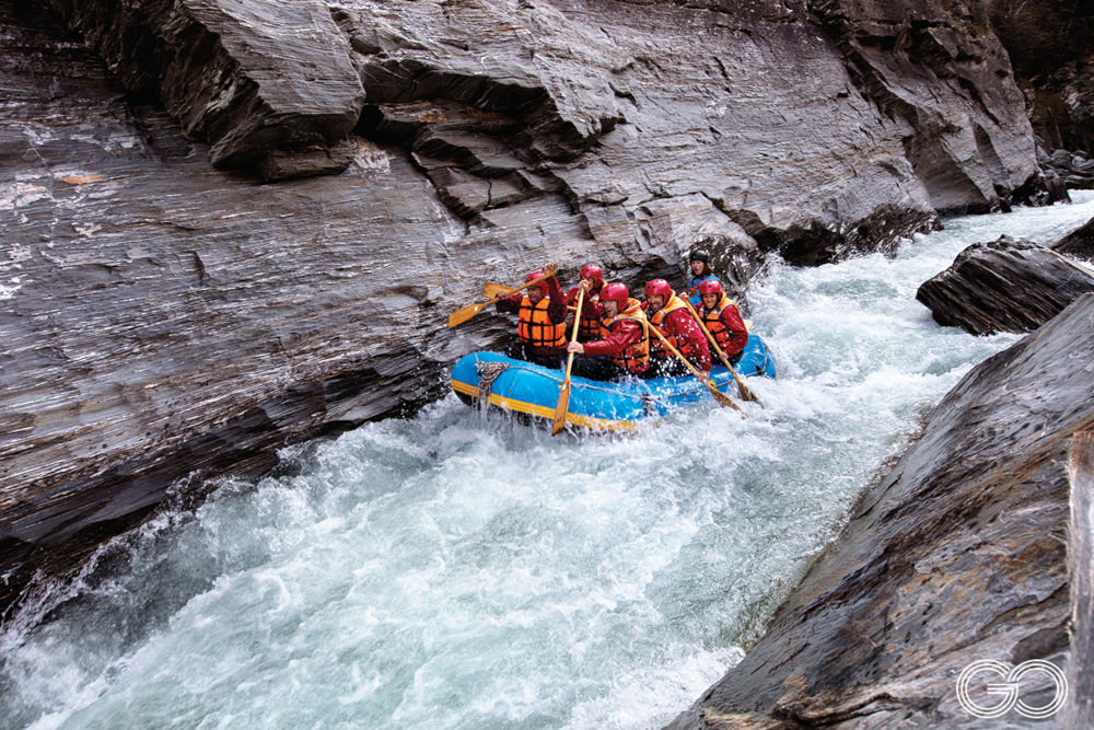 Raft on white water in narrow rocky canyon
